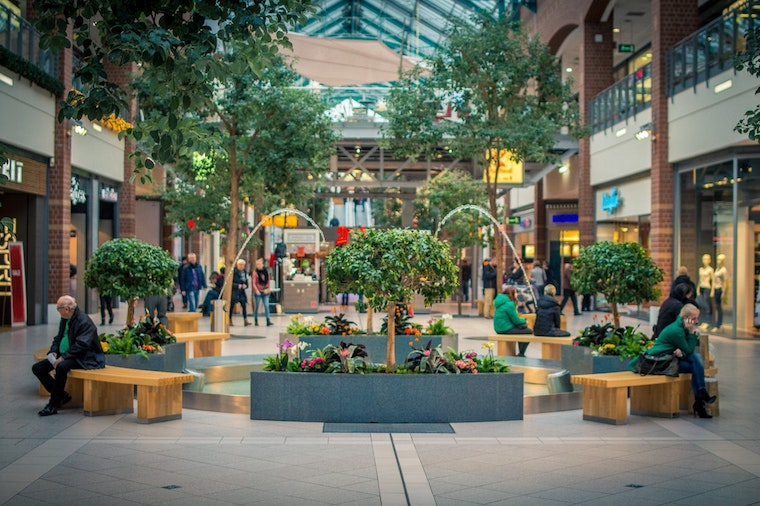 green shopping centre people sitting near trees
