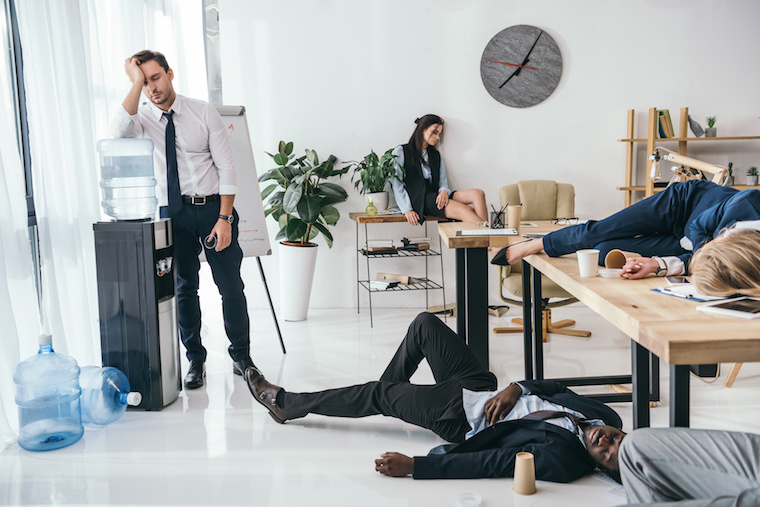 group of exhausted business partners sleeping at office