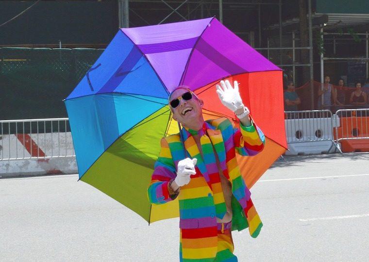 LGBTIQ+ man wearing rainbow suit holding rainbow umbrella