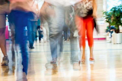 Abstract defocused motion blurred young people walking in the shopping center, urban lifestyle concept, background.