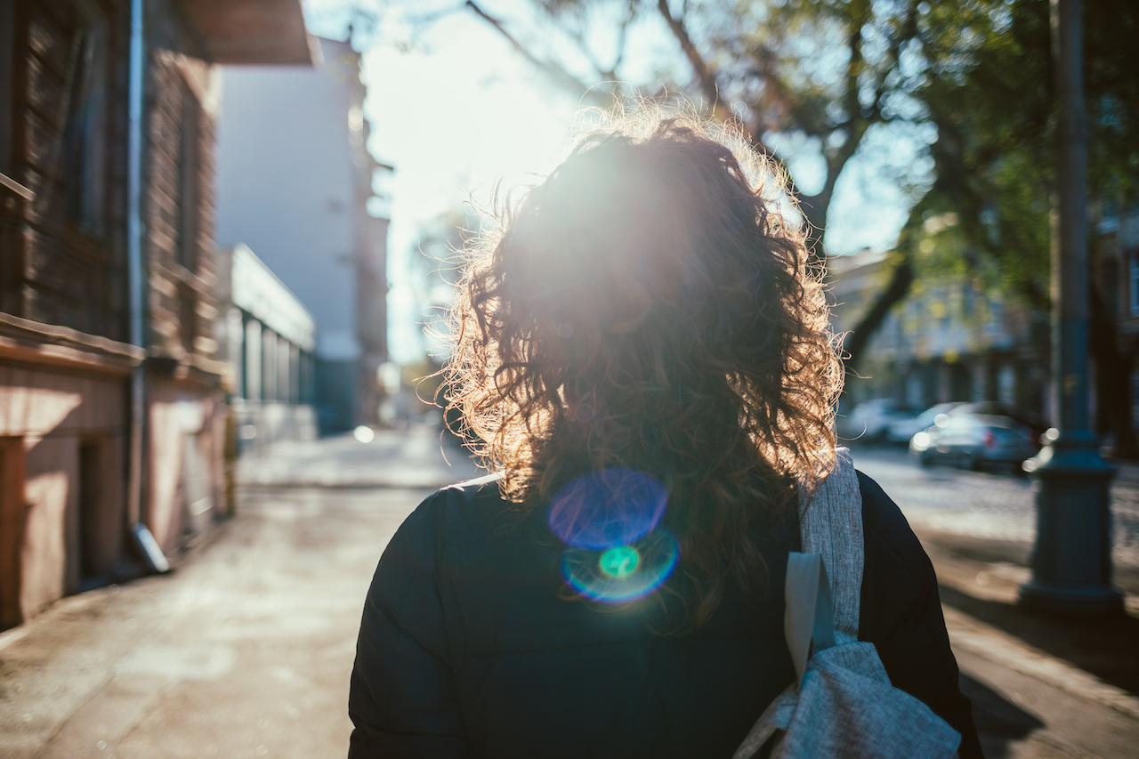 Rear view young woman walking down the street, sun flare towards her. Female with curly hair goes along city sidewalk.