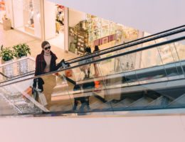 woman stands on shopping centre escalator