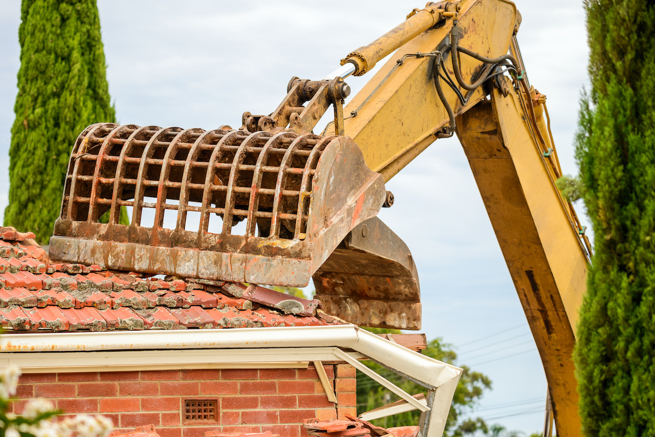 Old Australian suburban house demolition with excavator