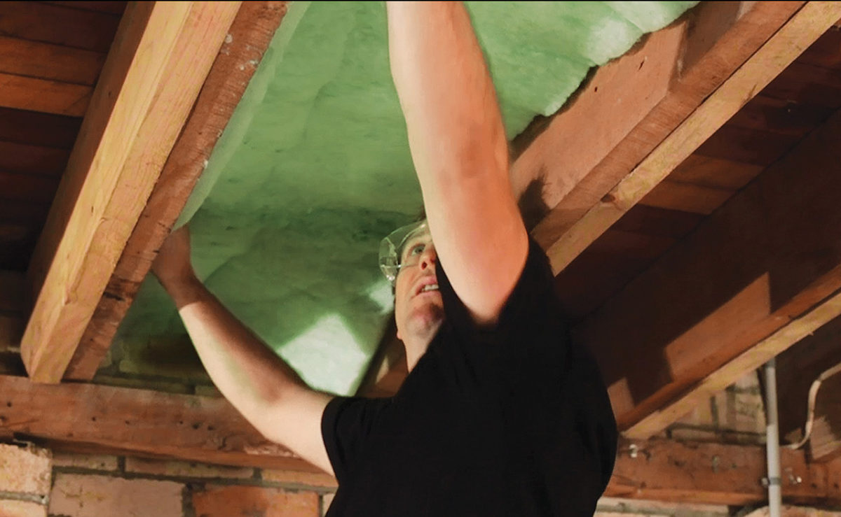 man installing roof insulation