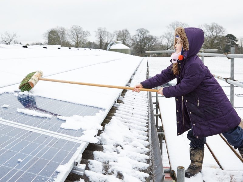 girl cleaning snow off solar panel